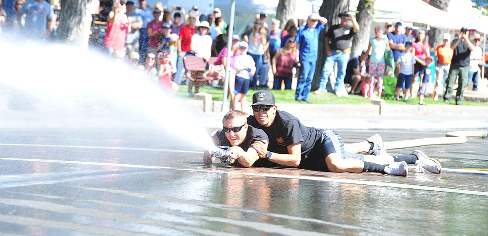 The Prescott National Forest Engine 930 takes the win during the annual Hose Cart Races and Bucket Brigade held in downtown Prescott Sunday July 1, 2018. The annual event recreates actual competitions held by early Prescott fire companies from the late 1880's like the Tough's Hose Company Number 1, the Dudes Hose Company Number 2, the Mechanics Hook and Ladder Company Number 1 and the O.K Hose Company Number 3. (Les Stukenberg/Courier)