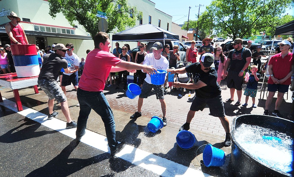 A team copmetes in a bucket brigade race during the annual Hose Cart Races and Bucket Brigade held in downtown Prescott Sunday July 1, 2018. The annual event recreates actual competitions held by early Prescott fire companies from the late 1880's like the Tough's Hose Company Number 1, the Dudes Hose Company Number 2, the Mechanics Hook and Ladder Company Number 1 and the O.K Hose Company Number 3. (Les Stukenberg/Courier)
