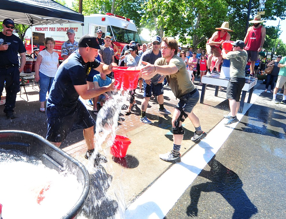 D shift competes in a bucket brigade during the annual Hose Cart Races and Bucket Brigade held in downtown Prescott Sunday July 1, 2018. The annual event recreates actual competitions held by early Prescott fire companies from the late 1880's like the Tough's Hose Company Number 1, the Dudes Hose Company Number 2, the Mechanics Hook and Ladder Company Number 1 and the O.K Hose Company Number 3. (Les Stukenberg/Courier)