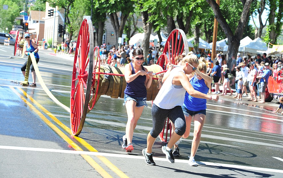 The ladies get involved during the annual Hose Cart Races and Bucket Brigade held in downtown Prescott Sunday July 1, 2018. The annual event recreates actual competitions held by early Prescott fire companies from the late 1880's like the Tough's Hose Company Number 1, the Dudes Hose Company Number 2, the Mechanics Hook and Ladder Company Number 1 and the O.K Hose Company Number 3. (Les Stukenberg/Courier)