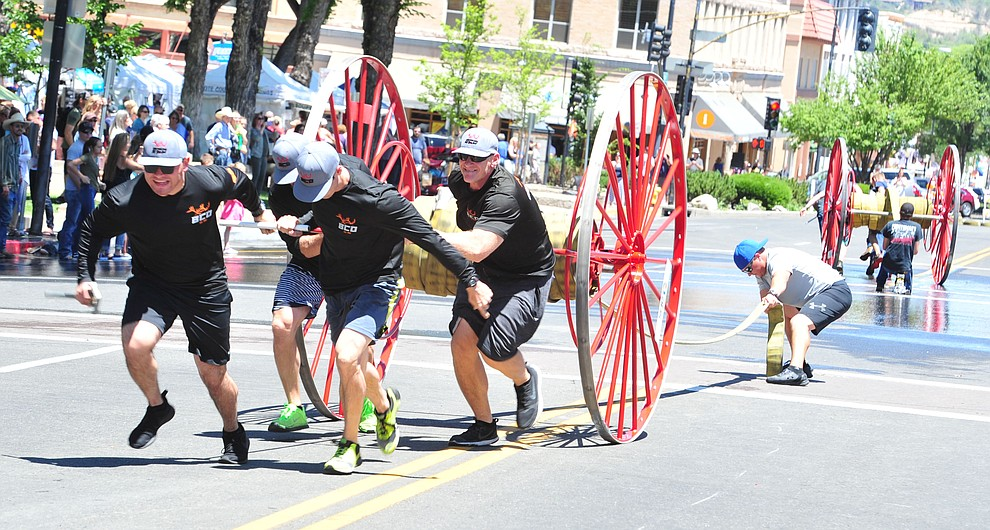 A team from Peoria Fire competes during the annual Hose Cart Races and Bucket Brigade held in downtown Prescott Sunday July 1, 2018. The annual event recreates actual competitions held by early Prescott fire companies from the late 1880's like the Tough's Hose Company Number 1, the Dudes Hose Company Number 2, the Mechanics Hook and Ladder Company Number 1 and the O.K Hose Company Number 3. (Les Stukenberg/Courier)