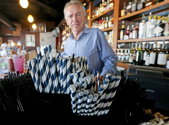 In this June 19, 2018 photo, paper straws sit at Duke Moscrip, owner of Duke's Restaurants, bar at his restaurant in Seattle. Businesses that sell food or drinks won't be allowed to offer the plastic items under a rule that went into effect Sunday, July 1. (Greg Gilbert/The Seattle Times via AP)