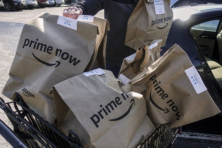 In this Feb. 8, 2018, file photo, Amazon Prime Now bags full of groceries are loaded for delivery by a part-time worker outside a Whole Foods store in Cincinnati. Amazon's Prime Day deals are coming to the aisles of Whole Foods, as the online retailer seeks to lure more people to its Prime membership after recently hiking up the price. (AP Photo/John Minchillo, File)