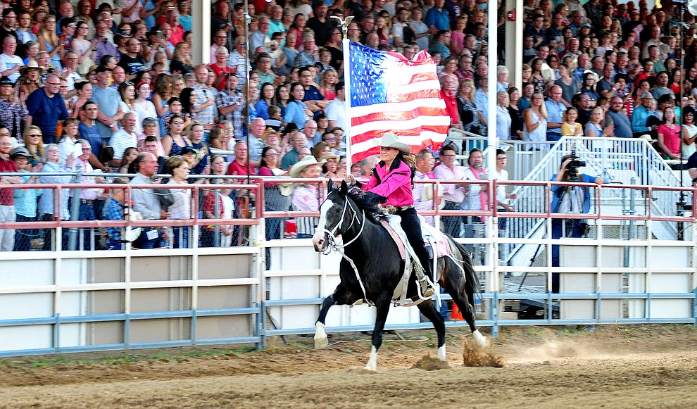 Sami Kilduff runs the American Flag during the 6th performance of the Prescott Frontier Days Rodeo Monday, July 2, 2018. (Les Stukenberg/Courier)