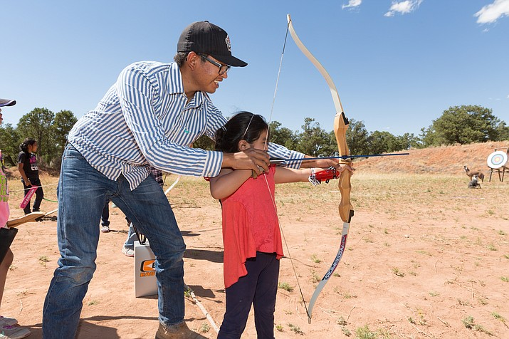 Tyler Begay assists Nyera Jones of Rock Point, Arizona, during the archery session of the Navajo Nation Girl Scouts STEM Camp June 23 in Tsaile. (Navajo Transitional Energy Company)