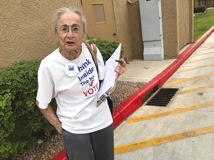 In this April 19, 2018, file photo, Rivko Knox, of Phoenix, a volunteer with the League of Women Voters, collects signatures for a ballot measure on campaign financing outside a polling station in Glendale, Ariz. A lawsuit filed Tuesday, July 3, 2018, on Knox's behalf, seeks to overturn a 2016 law that bars groups in Arizona from collecting early mail-in ballots from voters and delivering them as part of get-out-the-vote efforts. (AP Photo/Anita Snow, File)