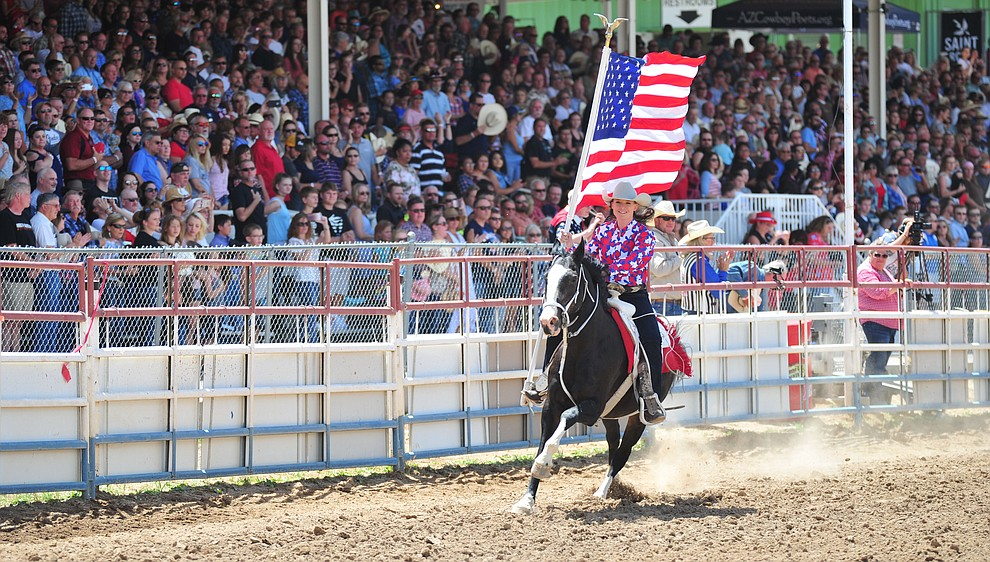 Sami Kilduff carries the American Flag during the final performance of the 2018 Prescott Frontier Days Rodeo Wednesday, July 4, 2018. (Les Stukenberg/Courier)