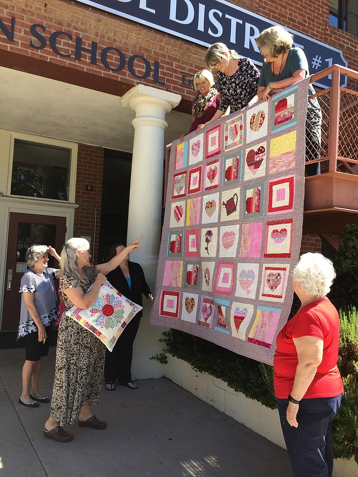 """""""Hannah's Heart"""" author and illustrator Diane Iverson points to some squares in the """"Hannah's Heart"""" raffle quilt crafted by five member of the Kwazy Kwquilters. The raffle quilt is to benefit the Coalition for Compassion and Justice and the Prescott Unified School District Family Resource Center. Left to right at top of stairs: CCJ Executive Director Jessi Hans, Kwazy Kwquilters founder Terri Capacete and Family Resource Center Coordinator Kelly Mattox. Behind Iverson, from left to right, are Quilter Patti Range and playwright Melanie Ewbank. At right front is Quilter Debbie Waters."""