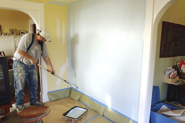 Painting contractor Andrew Lohr finishes the first coat on his living room wall. A fresh coat of paint on the walls can make for a quick makeover. (Greg Wahl-Stephens/AP, file)
