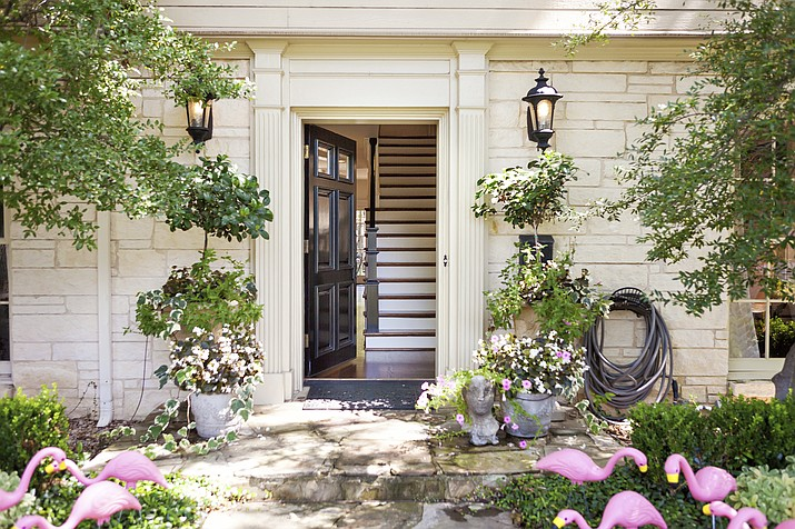 The delicate leaves and flowers of potted flowering plants can create a perfect balance with the architectural molding and a dramatic black front door, such as at this entryway designed by Abbe Fenimore of Studio Ten 25 in Dallas, Texas. (Melanie Johnson Photography/Abbe Fenimore via AP)