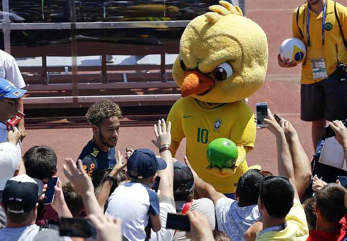 """Brazil's mascot holds a soccer ball as fans cheer Brazil's Neymar as he leaves a training session in Sochi, Russia, on June 12, 2018. It took an angry-looking bird to get Brazilians hooked on their World Cup mascot. Brazil historically never fully embraced the tradition of mascots in sports, but things changed when the soccer federation — inspired in part by Chicago Bull's """"Benny the Bull"""" — turned its cute-looking """"Canary"""" into a mean figure that represents the fans' anger following the humiliating home loss at the World Cup four years ago. (Andre Penner/AP Photo, file)"""