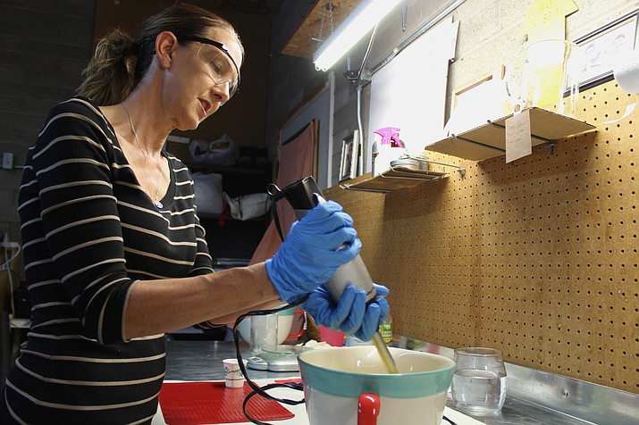 Jenny Wassell whips up a batch of her sandalwood and petrulli oil soap. (Vanessa Espinoza/Daily Miner)