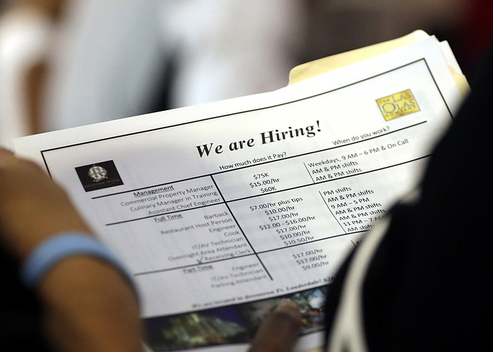 In this Thursday, June 21, 2018 photo, a job applicant looks at job listings for the Riverside Hotel at a job fair hosted by Job News South Florida, in Sunrise, Fla. The Labor Department said Friday, July 6, that the unemployment rate rose to 4.0 percent from 3.8 percent as more people began looking for work and not all of them found it. (AP Photo/Lynne Sladky)
