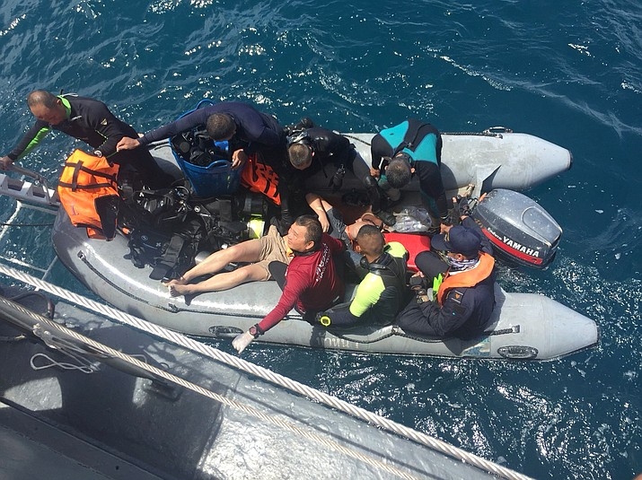 Divers on a rubber raft retrieve a body during a search operation in the water off Phuket, Thailand, Friday, July 6, 2018. Thai divers scoured the wreckage of a boat with Chinese tourists that sank in a storm off the resort island of Phuket. (AP Photo)