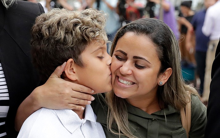 Diego Magalhaes, left, 10, kisses his mother Sirley Silveira, Paixao, an immigrant from Brazil seeking asylum with her son, after Diego was released from immigration detention, in Chicago. (AP Photo/Charles Rex Arbogast)