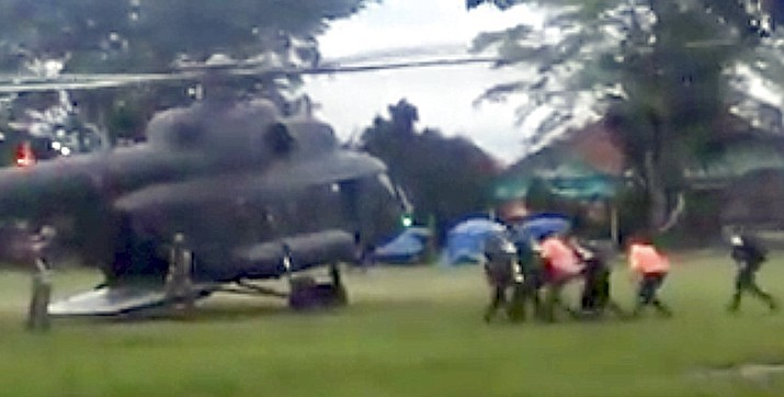 In this image made from video taken Sunday, July 8, 2018, an emergency team carries a stretcher believed to be carrying one of the rescued boys from the flooded cave to a waiting helicopter in Mae Sai, Chiang Mai province, northern Thailand. (Big Krean)
