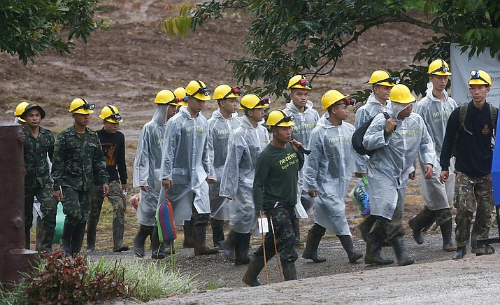 In this Tuesday, July 10, 2018 photo, rescue workers walk toward the entrance to a flooded cave complex where  12 young soccer players and their coach were trapped for 18 days in Mae Sai, Chiang Rai province, northern Thailand. (AP Photo/Sakchai Lalit)