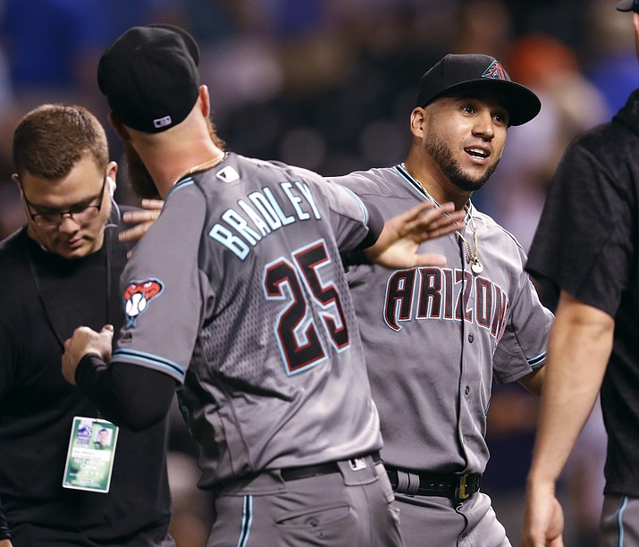 Arizona Diamondbacks relief pitcher Archie Bradley, left, congratulates right fielder David Peralta after the team's 5-3 win in a baseball game against the Colorado Rockies on Tuesday, July 10, 2018, in Denver. (David Zalubowski/AP Photo)