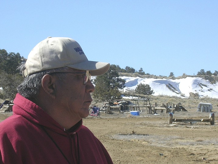 Teddy Nez stands on his property in northwestern New Mexico on March 12, 2008. Behind him is a 50-foot uranium waste pile from mining operations. (Felicia Fonseca, AP Photo File)