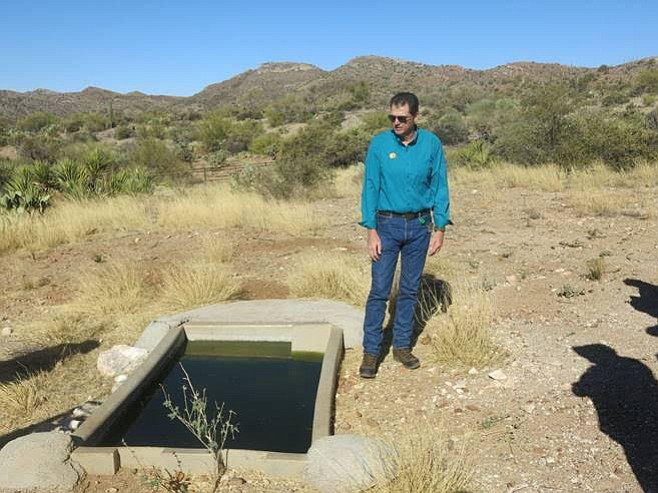 Joe Currie, programs director at the Arizona Game & Fish Department, stands by a water catchment near Superior. (Photo/Arizona Game & Fish Department)