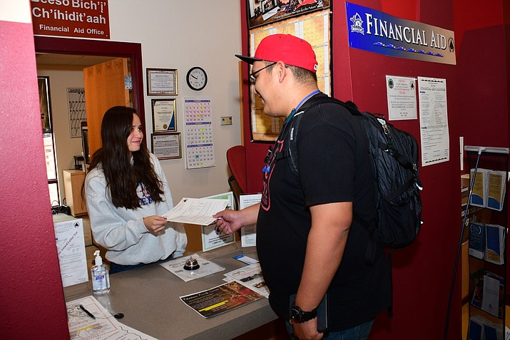 Registration office aide Moretta Bia assists Darren Williams, a student at Diné College.  (Ed McCombs/Diné College)