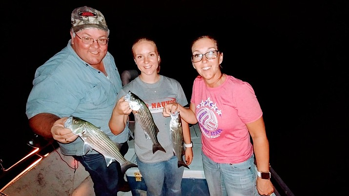 Kevin Burgess, his daughter LaNae and wife Darlynn, show the three stripers they caught at the same time while fishing at Lake Mead on Saturday night. Photo by Don Martin.