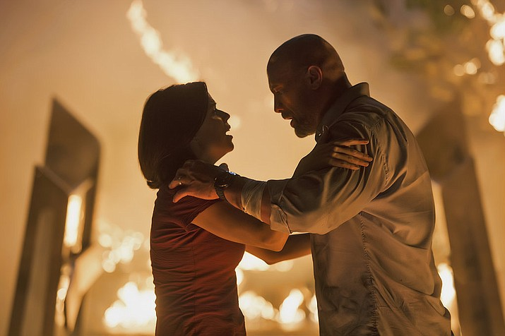 "This image released by Universal Pictures shows Neve Campbell, left, and Dwayne Johnson in a scene from ""Skyscraper."" (Kimberley French/Universal Pictures)"
