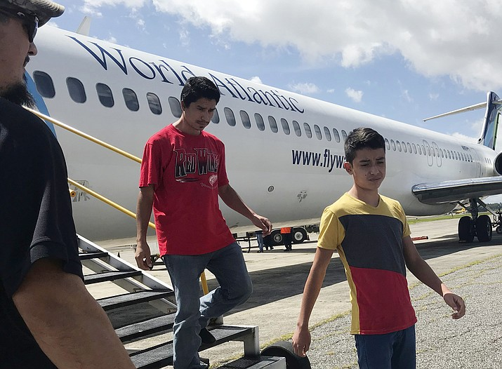 Fourteen-year-old Hermelindo Juarez, right, and his father, Deivin Juarez, step off a chartered flight from the U.S., Tuesday, July 10, 2018 in Guatemala City, Guatemala, after the two were deported. They were separated for weeks and Juarez said he wasn't sure he'd see his son again. (AP Photo/Colleen Long)