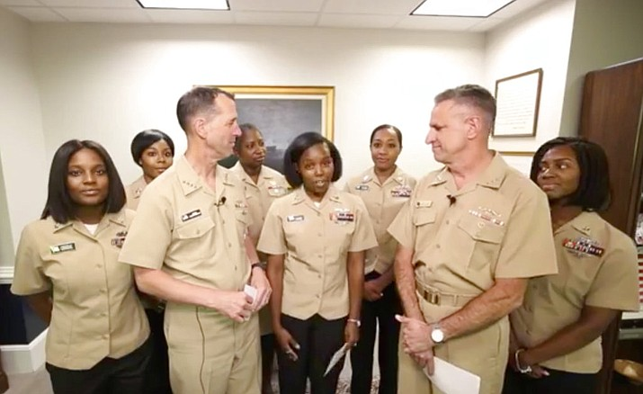 In this frame grab from a Facebook Live event Tuesday, July 10, 2018, by the U.S. Navy, Yeoman First Class LaToya Jones, center, speaks as Chief of Naval Operations Adm. John Richardson, left of center, and Chief of Naval Personnel Adm. Robert Burke, right of center, and other members of the working group listen. The Navy says it will now allow servicewomen to sport ponytails and other hairstyles, reversing a policy that long forbade females from letting their hair down. (Courtesy of U.S. Navy via AP)