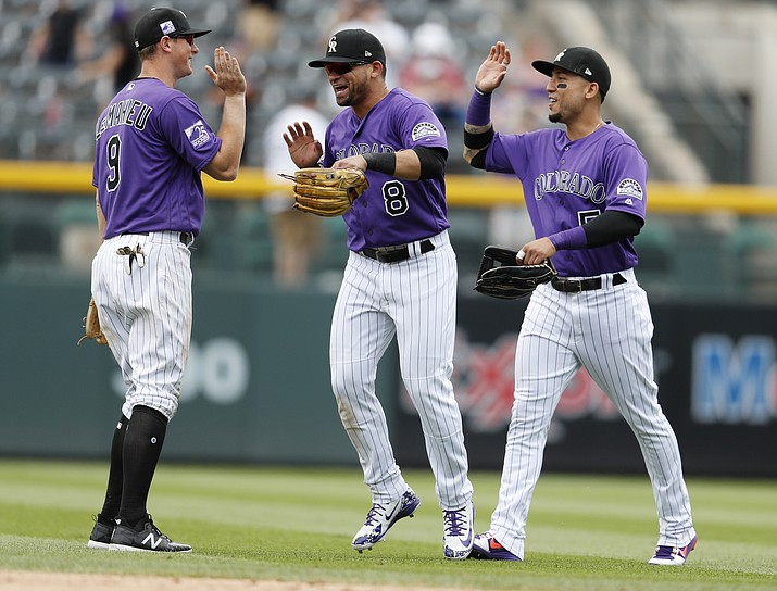 Colorado Rockies second baseman DJ LeMahieu, left fielder Gerardo Parra and right fielder Carlos Gonzalez, from left, celebrate the team's 5-1 win against the Arizona Diamondbacks in a baseball game Thursday, July 12, 2018, in Denver. (David Zalubowski/AP Photo)