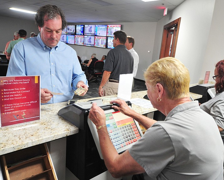 Co-owner Tom Auther makes a bet as Arizona Downs opened its doors for off-track betting for horse races across the country Friday, July 13, 2018. (Les Stukenberg/Courier)