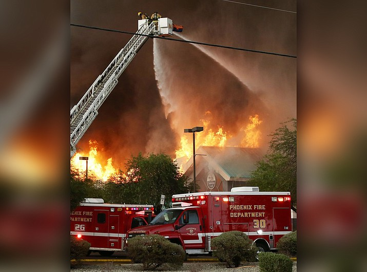 Phoenix and Glendale, Arizona fire departments battle a fire Wednesday, July 11, 2018 in Phoenix. The fire gutted a supermarket in west-central Phoenix during a heavy rainstorm storm Wednesday evening and authorities were trying to determine if the building was struck by lightning. (AP Photo/Rob Schumacher/The Arizona Republic)