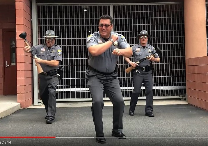 "Mohave County Sheriff Doug Schuster (center), with Chief Deputy Dean McKie and Undersheriff Ed Trafecanty perform a lip-synced rendition of Johnny Horton's ""The Battle of New Orleans"" for the law enforcement ""Lipsync Challenge"" on YouTube. (Photo courtesy Mohave County Sheriff's Department)"