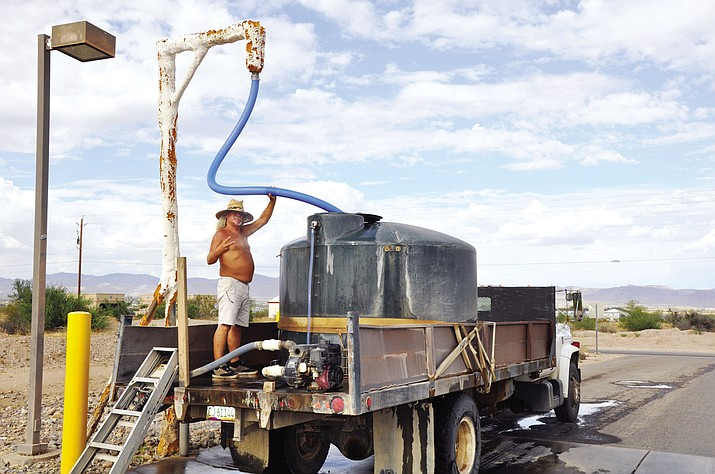 Carl Smith, one of the two professional water haulers in Golden Valley, fills the 1,500 gallon tank on his truck at the GVID standpipe located at Bolsa Drive and Estrella Road in Golden Valley. Smith is known valley-wide for never wearing a shirt and flashing the peace sign to everyone he sees. (Photo by Butch Meriwether for the Daily Miner)