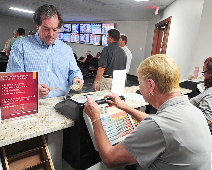 Co-owner Tom Auther makes a bet as Arizona Downs opened its doors for off-track betting for horse races across the country Friday, July 13, 2018. (Photo by Les Stukenberg/Daily Courier)