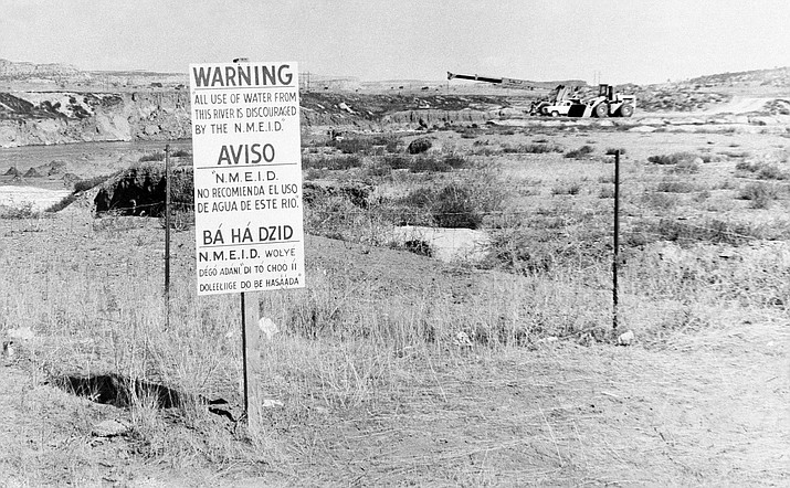 In this Nov. 13, 1979, file photo, while United Nuclear Corp. uses a combination of hand work and heavy machinery to clear up a uranium tailings spill, signs along the Rio Puerco warn residents in three languages to avoid the water in Church Rock, N.M. The Navajo Nation is urging Congress to expand a federal law that compensates people exposed to radiation. (AP Photo/SMH, File)