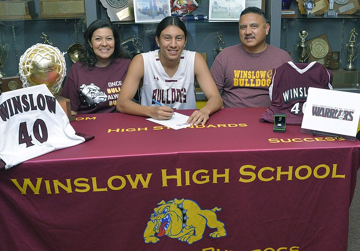 Ricardo Villanueva Jr. is flanked by his parents as he receives an athletic scholarship to American Indian College. (Photo/Todd Roth)
