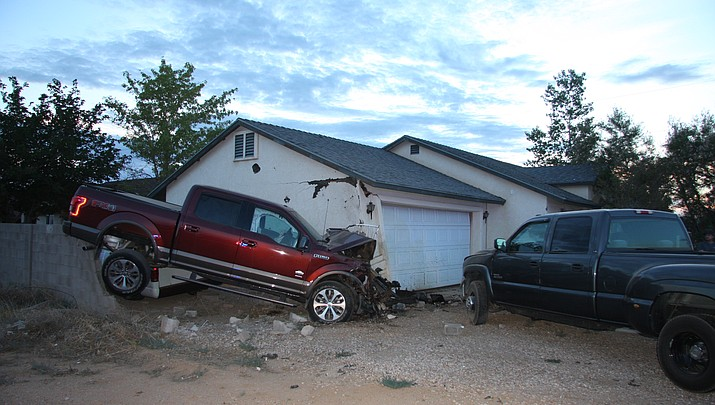 Woman crashes truck through block wall into house, parked vehicles