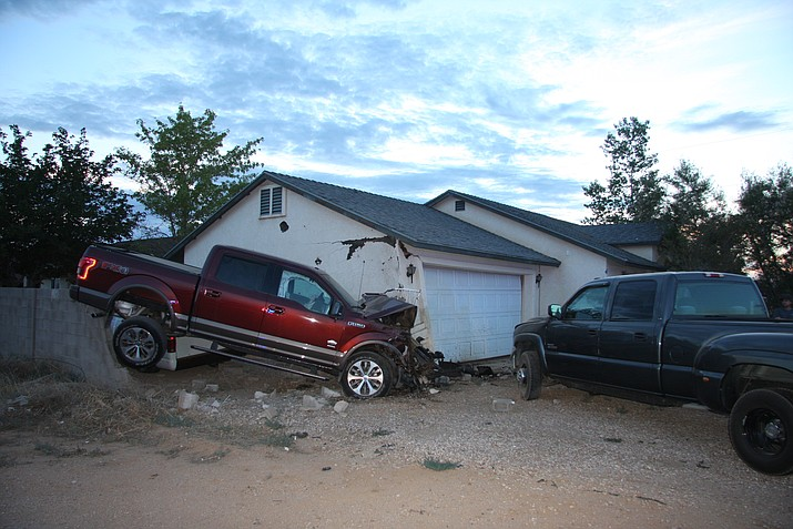 A 71-year-old woman behind the wheel of the red Ford F-150 suffered injuries to her pelvis or hip after going through a block wall and crashing into two parked vehicles and a house in the 3700 block of Irving Street Saturday morning. (Kingman Police Department photo)