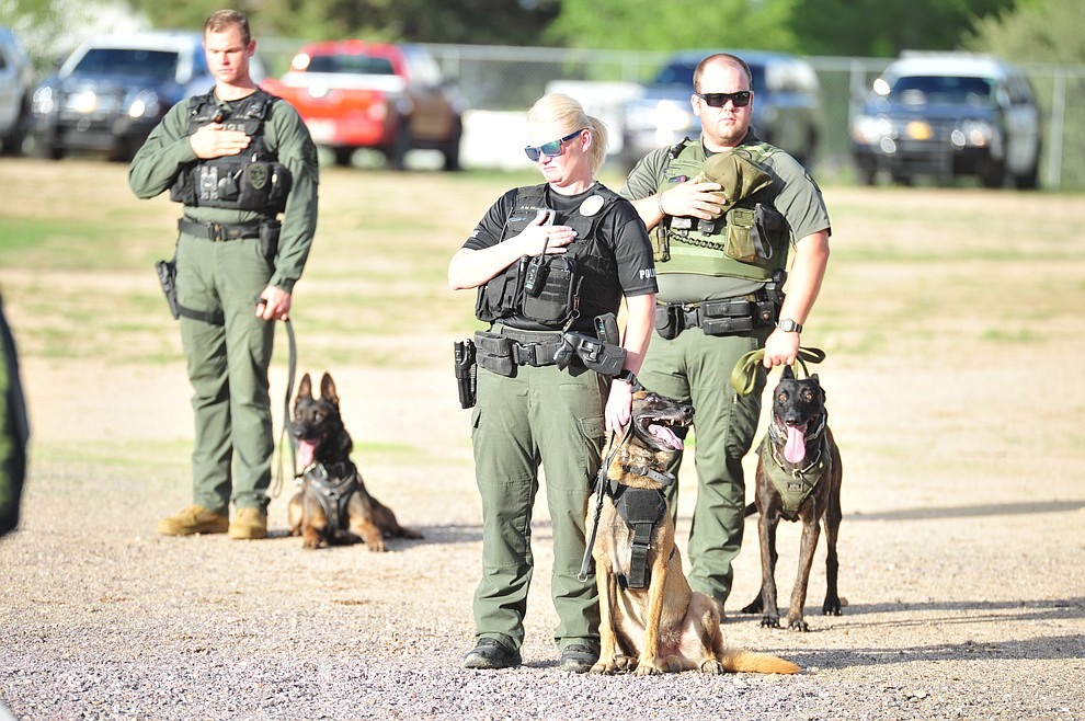 Officers stand for the National Anthem as police K-9 handlers and their partners from throughout Arizona who are attending the 26th annual Canine Survival Seminar at Yavapai College hold a public demonstration at the Prescott Rodeo Grounds Tuesday, July 17, 2018.(Les Stukenberg/Courier)