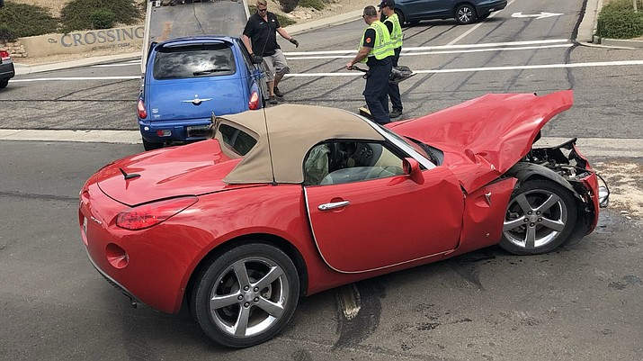 Rescue crews from Prescott Fire work a crash scene Tuesday morning, which involved this Pontiac Solstice. The two people were treated and transported to the hospital, said Jeff Jones, Prescott firefighter and paramedic. (Prescott Fire/Courtesy)