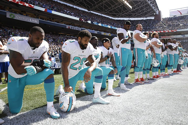 FILE - In this Sept. 11, 2017 file photo, from left, Miami Dolphins' Jelani Jenkins, Arian Foster, Michael Thomas, and Kenny Stills, kneel during the singing of the national anthem before an NFL football game against the Seattle Seahawks in Seattle. Miami Dolphins players who protest on the field during the national anthem this season could be suspended for up to four games under a new team policy issued to players this week. (AP Photo/Stephen Brashear, File)