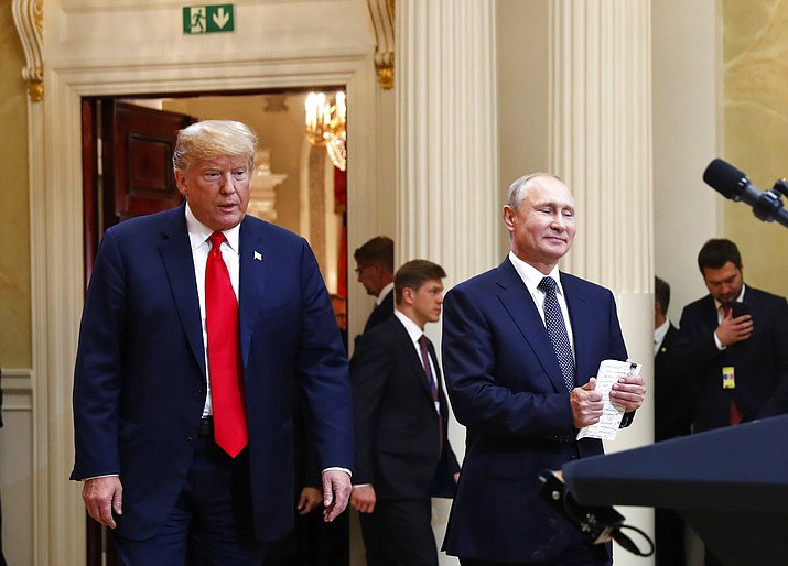 In this July 16, 2018, photo, U.S. President Donald Trump, left, and Russian President Vladimir Putin arrive for a news conference at the Presidential Palace in Helsinki, Finland. Trump has asked national security adviser John Bolton to invite Putin to Washington in the fall. That's the latest update Thursday from White House press secretary Sarah Huckabee Sanders following Trump's meeting with Putin earlier this week in Finland. (AP Photo/Pablo Martinez Monsivais)