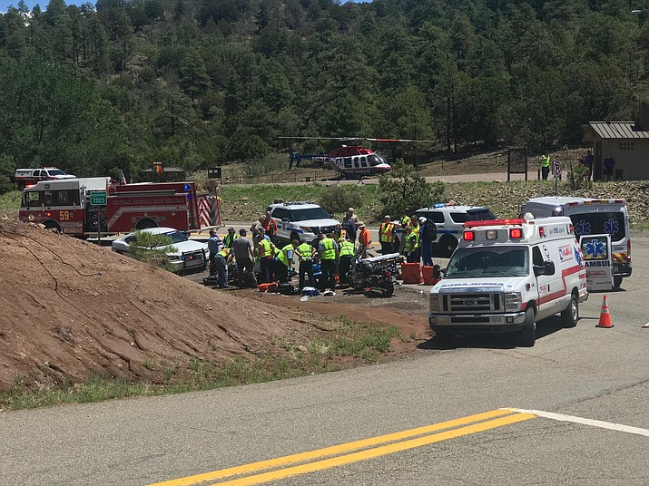 Emergency personnel assist two motorcycles riders who were injured in a crash near the Mingus Mountain Recreation Area on Highway 89A late Thursday morning, July 19.
