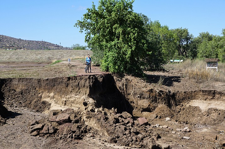Theresa Ditson of Prescott stands on the far side of the hole that was gouged into the Peavine Trail by an intense rainstorm Wednesday, July 18. Ditson was among the cyclists out Thursday morning, who were surprised by the extent of the damage. (Cindy Barks/Courier)