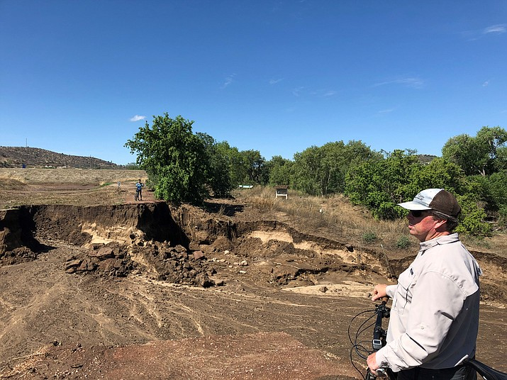 Bicyclists pause Thursday morning, July 19, on the Peavine Trail where the trail and a lot more has been washed away by rainfall. (Cindy Barks/Courier)