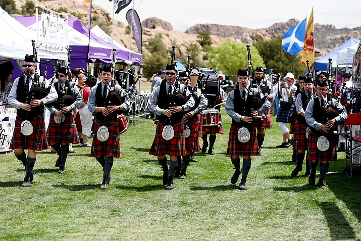 In this file photo the Phoenix Pipe Band marches through a crowd of locals and tourists during the 2016 Highland Games at Watson Lake Park in Prescott. A new report commissioned by the state Office of Tourism says tourism spending in Arizona totaled $22.7 billion last year, an increase of nearly 7 percent from the previous year. (Les Stukenberg/The Daily Courier)
