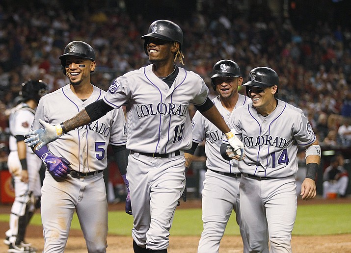 Colorado Rockies' Raimel Tapia (15) celebrates his grand slam off Arizona Diamondbacks' Archie Bradley with Carlos Gonzalez (5), Gerardo Parra and Tony Wolters (14) during the seventh inning during a baseball game Friday, July 20, 2018, in Phoenix. (Darryl Webb/AP)