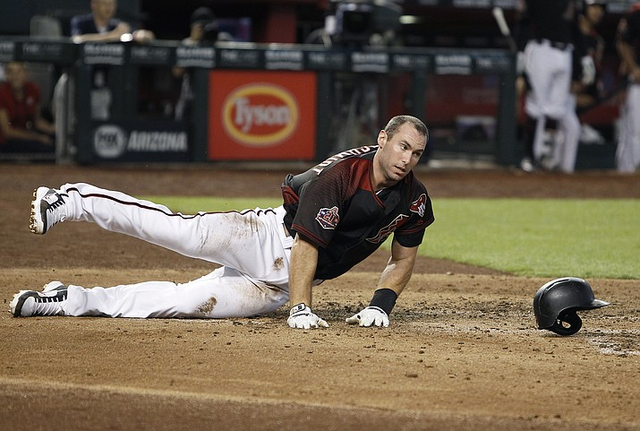 Arizona Diamondbacks' Paul Goldschmidt loses his helmet as he slide across home plate to score against the Colorado Rockies on a sacrifice fly by Nick Ahmed during the fourth inning of a baseball game Saturday, July 21, 2018, in Phoenix. (Ralph Freso/AP)