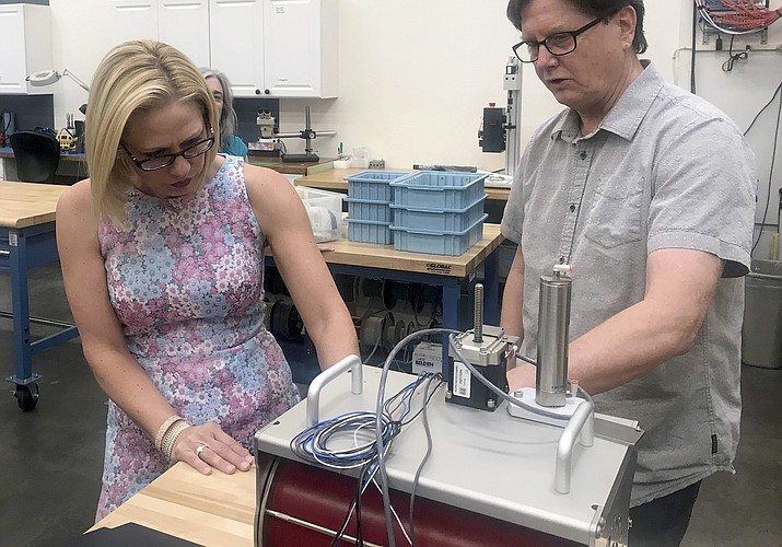 Rep. Krysten Sinema visits Blockwise Engineering in Tempe, Ariz., on July 2, 2018, and speaks with company founder Ed Goff about his company's manufacturing process. Sinema has come a long way from her days as a Green Party activist as she seeks to become the first Democrat to represent Arizona in the Senate in 30 years. (AP Photo/Melissa Daniels, file)